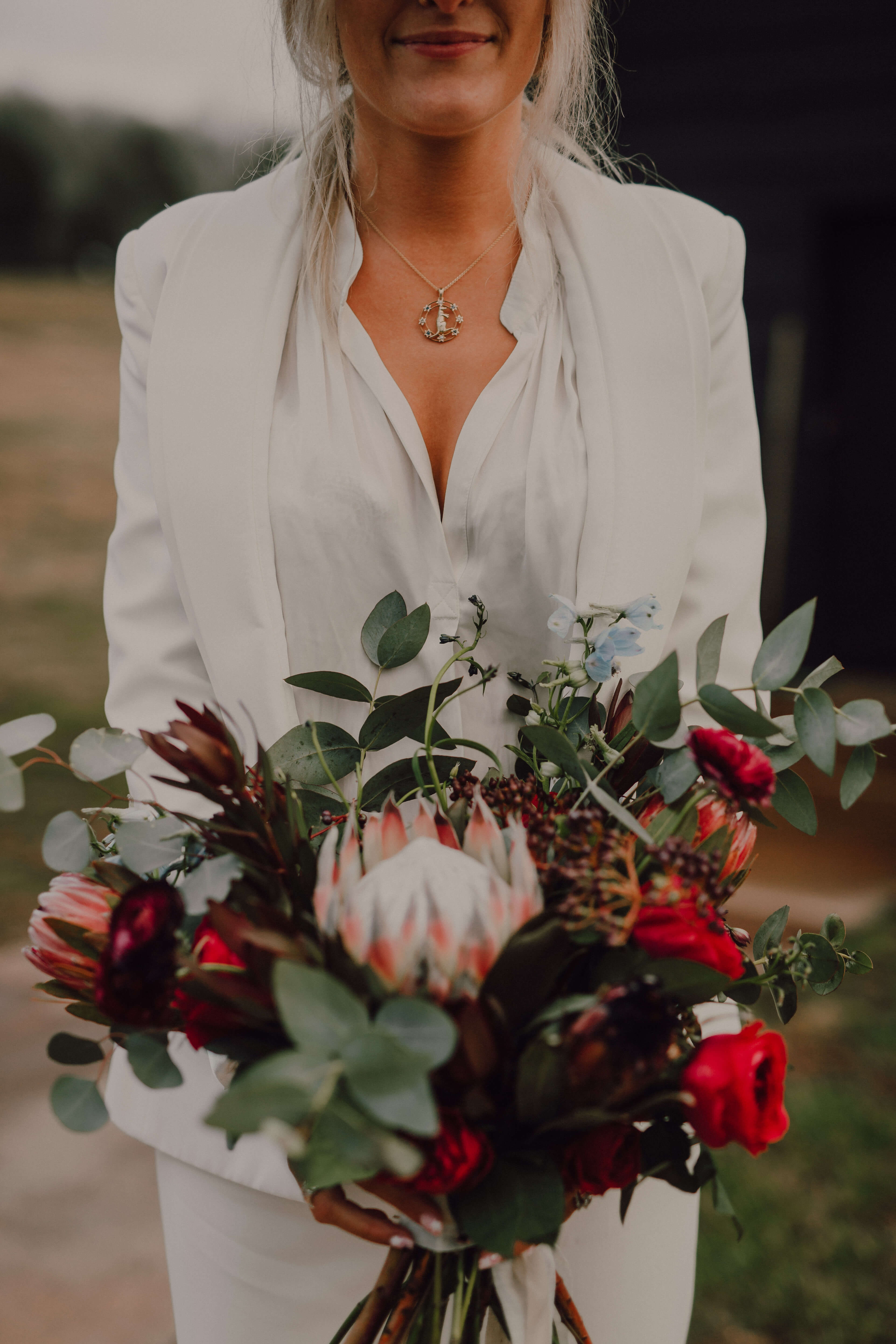 Wild bouquet with deep reds and king protea | Winter wedding bouquet in Nashville, TN | Arrington Vineyards wedding | Cause We Can Events