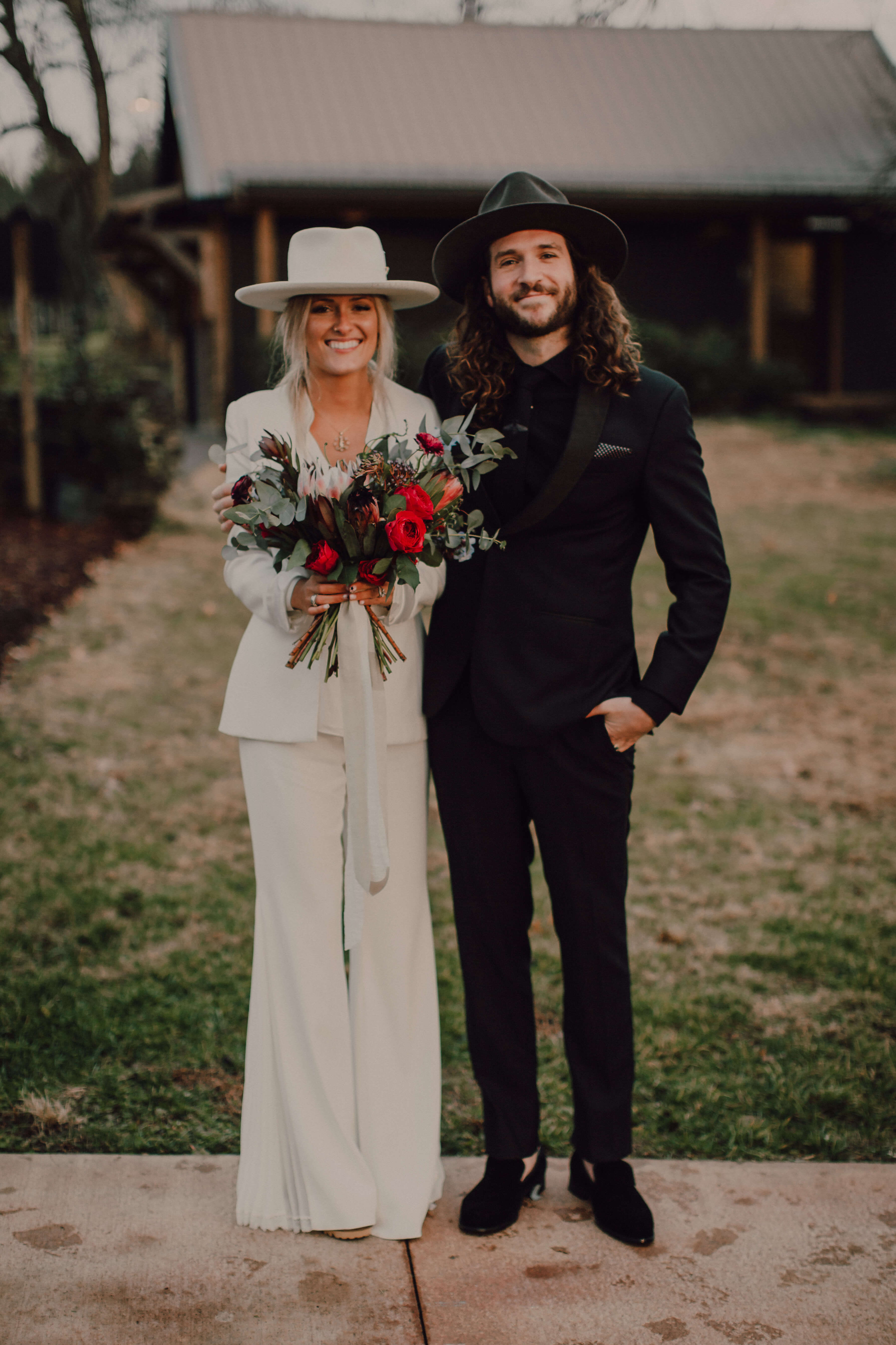 Trendy bride and groom in black and white. Bride in pant suit with boho hat | Nashville wedding elopement | Arrington vineyards