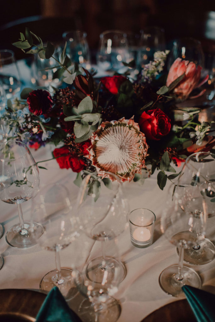 Gorgeous centerpiece with king protea and dark red flowers on white table cloth | Nashville wedding