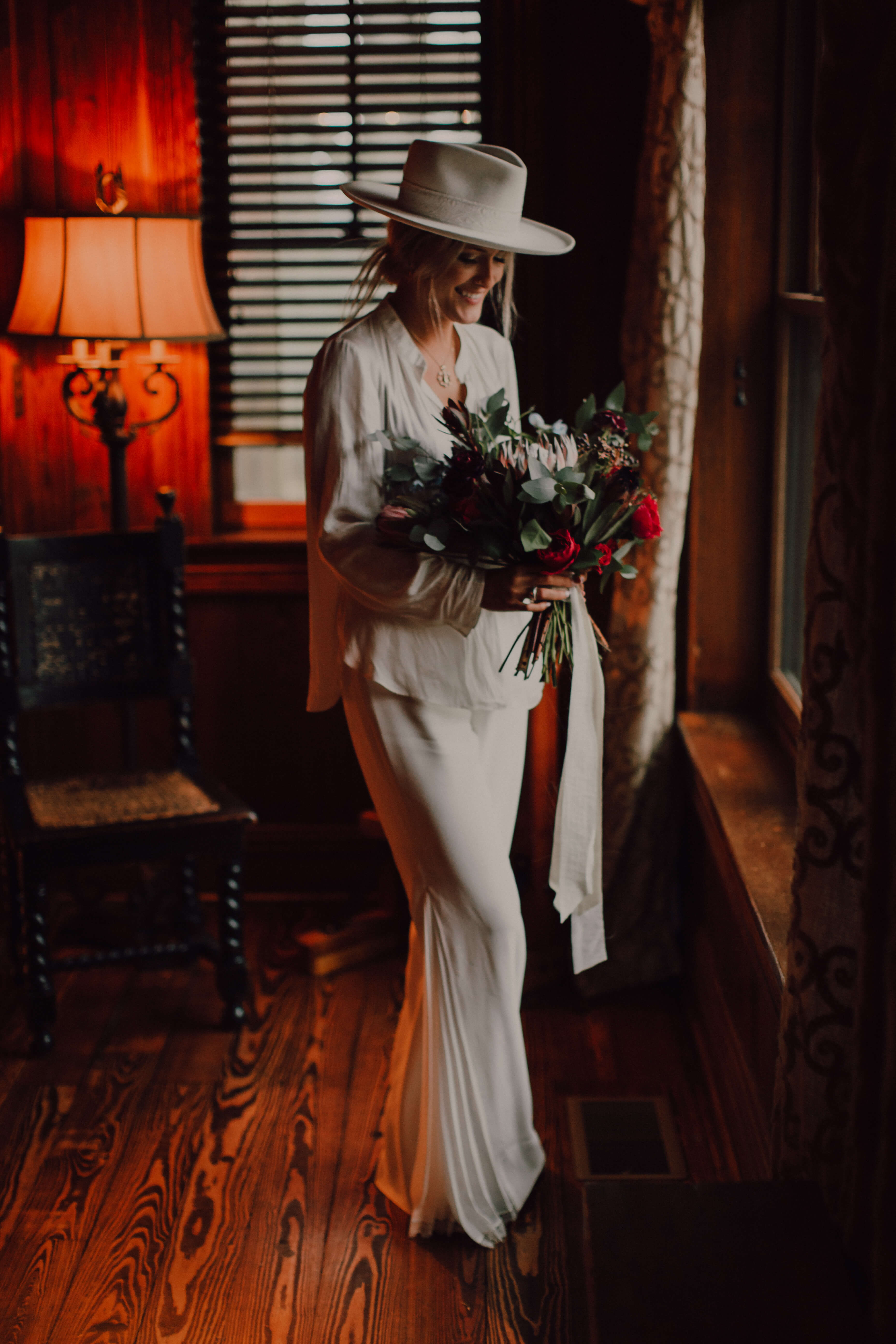 Bride in white bellbottoms and white blazer with white hat holding bouquet with king protea. Nashville wedding elopement | Adventurous Wedding in Nashville