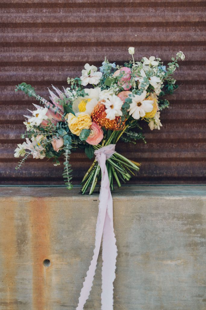 Wild bouquet with muted yellows, pinks and king protea flowers by best Day ever floral design