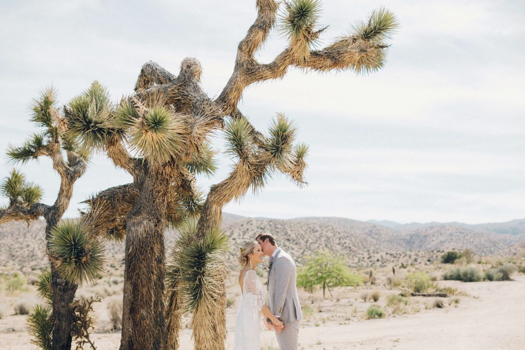 Bohemian bride and groom kissing at desert wedding in Joshua Tree