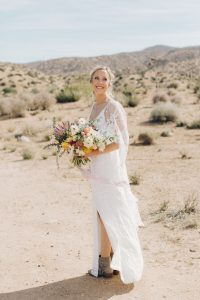 Bride in the desert wearing Grace Loves Lace dress with wings and wild bouquet wit yellow, white and pink flowers