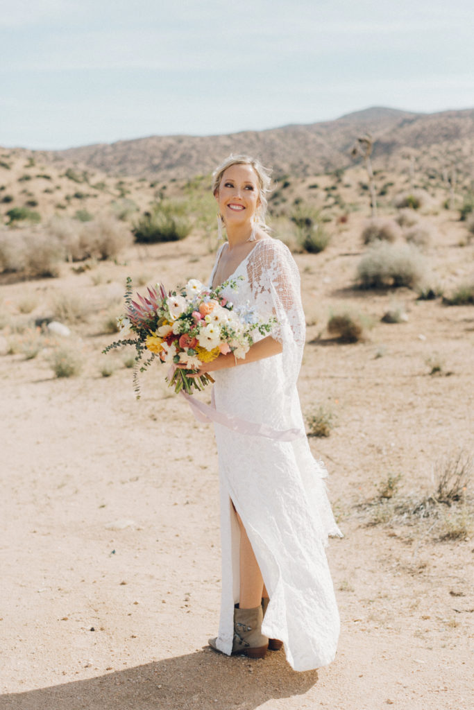 Bride wearing Grace Loves Lace wedding gown with wings and brown boots for her desert wedding at Rimrock Ranch. Joshua Tree wedding designed and planned but destination wedding planner Cause We Can Events