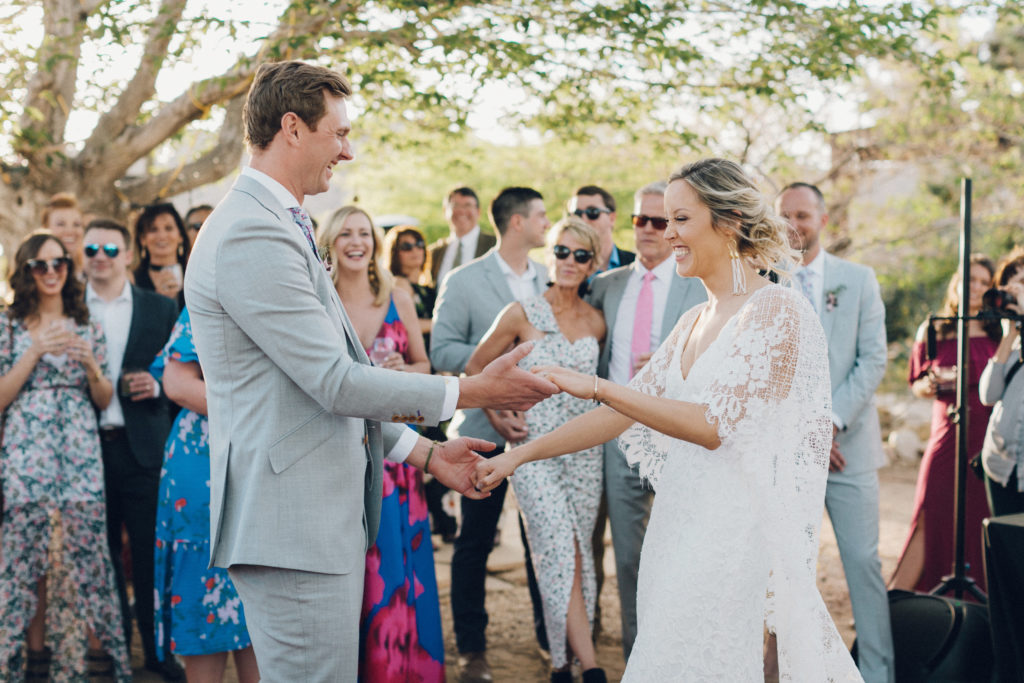 Bride and groom first dance at Rimrock Ranch in Joshua Tree. Desert wedding with groom in light grey suit and bride in Grace loves Lace dress with wings