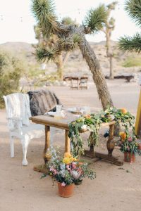 Sweetheart table in the desert with long green garland and pops of mustard yellow flowers. Chairs covered with fur blankets for a boho look