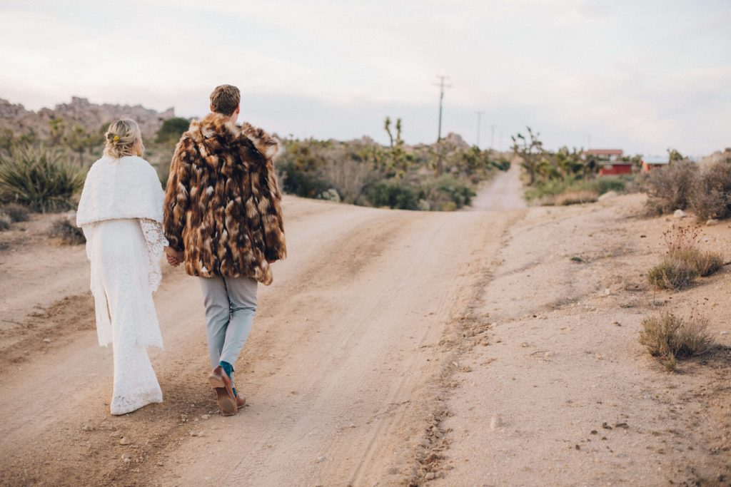 Bride and groom in the desert with faux fur coats. Burning man inspired wedding fashion