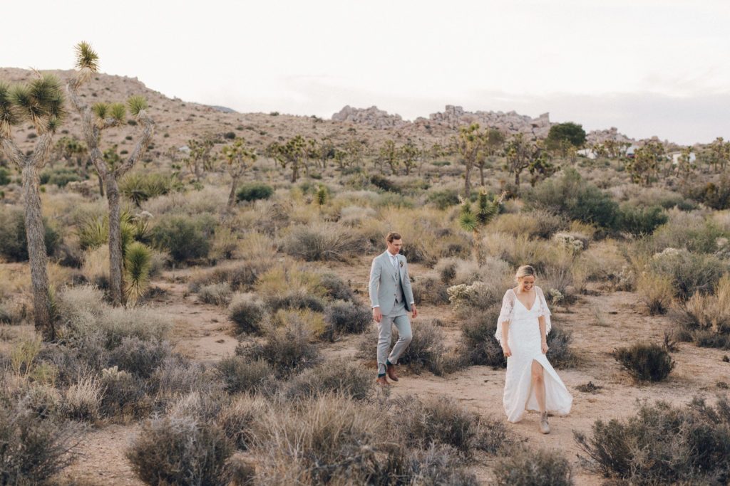 Bride and groom walking through the desert in Joshua Tree. Desert wedding at Rimrock Ranch in Joshua Tree, CA. Destination wedding planner Cause We Can Events