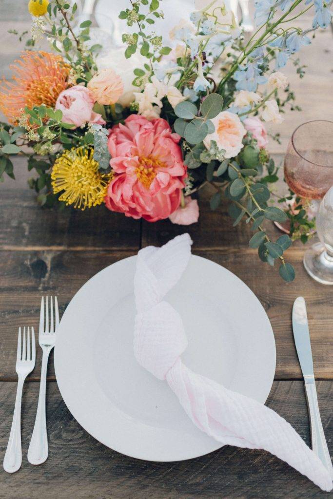 Long wooden table with white plates, knotted light pink napkins and silver flatware. Blush and clear wine glasses added a pop of color. The centerpieces were bright with pops of yellow, pink and white. Each table was decorated with a few airplants.