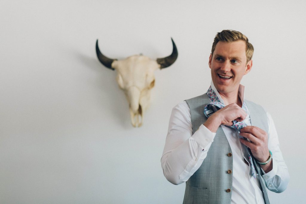 Groom getting ready with cow skull on the wall. Groom wearing light great vest with white button shirt