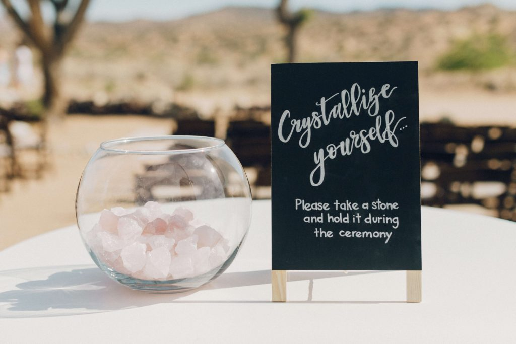 Unique ceremony idea: Signage with bowl of rose quartz where guests can pick one up, give it good energy and place it back for the newlyweds to keep.
