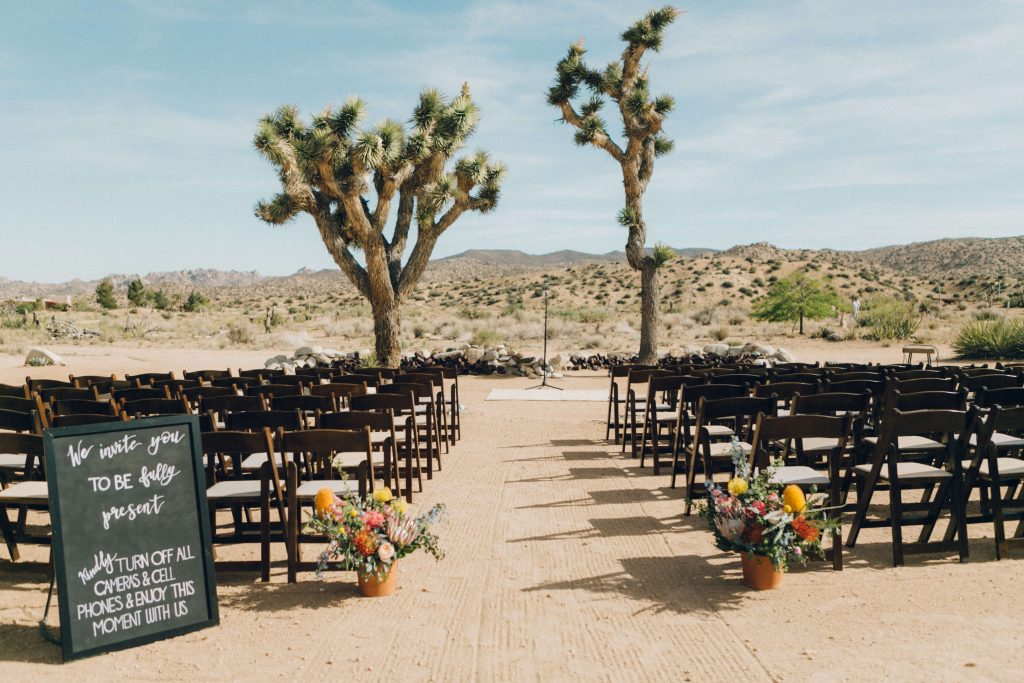 Ceremony set up at Rimrock Ranch in Joshua Tree, CA. Gorgeous ceremony with yucca trees and the desert in the back drop. Dark wooden chairs with floral arrangements in terracotta pot