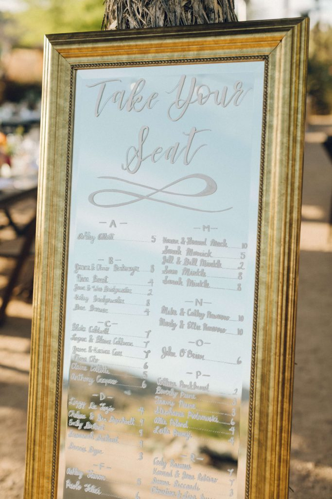 Wedding seating chart written on tall gold mirror