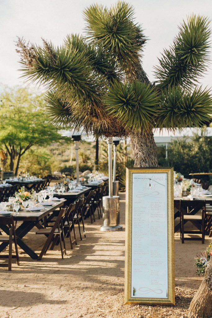 Seating chart written on tall mirror with gold frame at desert wedding
