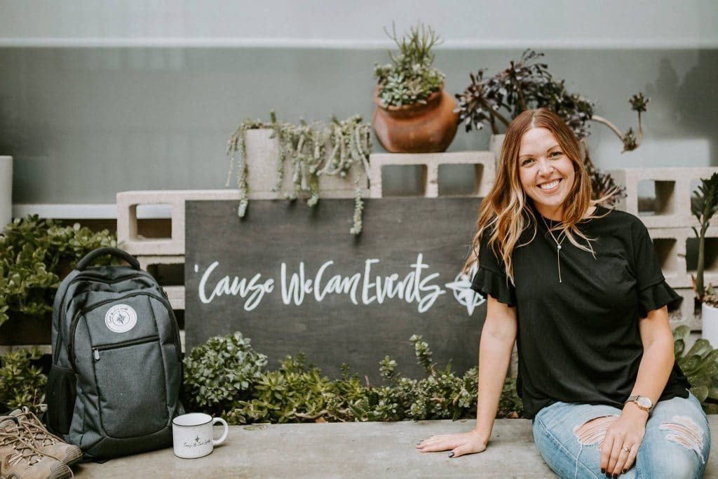 Event Planner, Gabby Pinkerton of Cause We Can Events with branded mug and logo on wooden sign. Succulent garden with concrete walls for lifestyle shoot in Long Beach, CA