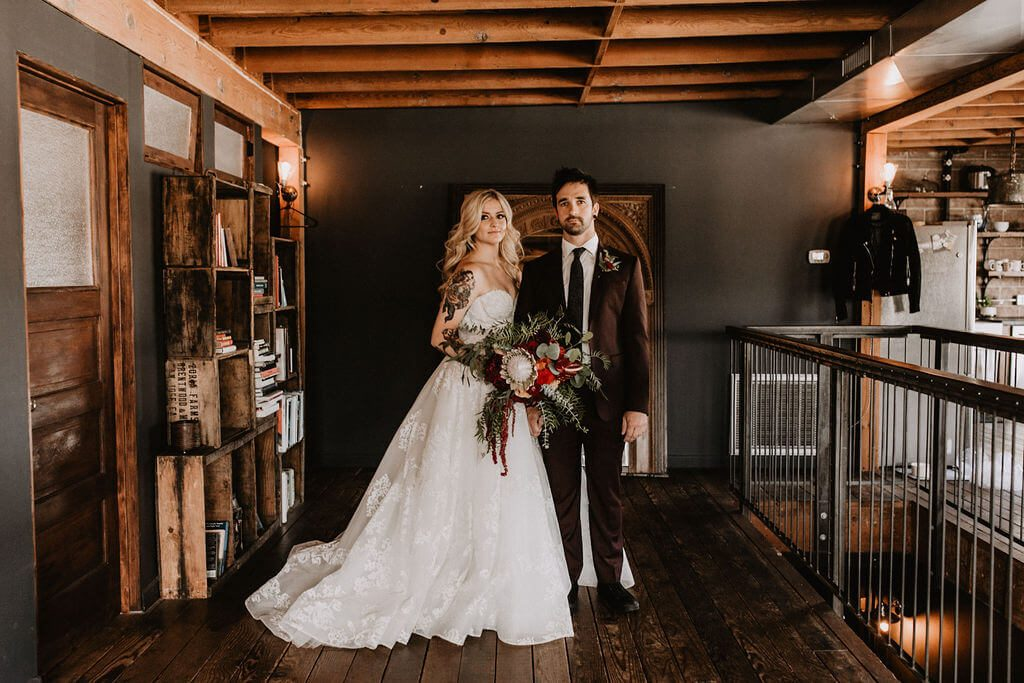Tattooed bride in sweetheart ball gown at Smoky Hollow Studios. Warehouse wedding with arcade games, smoke bombs and moody florals