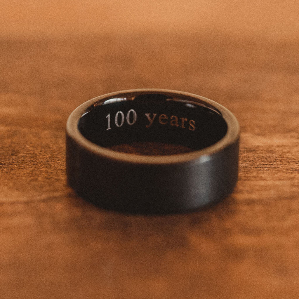 "Groom's black wedding band with engravment that says ""100 years"""