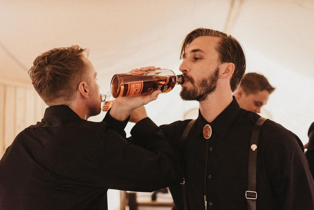 Groom and groomsmen sharing a bottle of whiskey before the wedding. Groom wearing an all black suit and shirt.