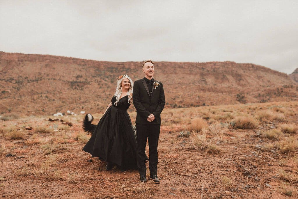 Bride and groom in all black in desert at Zion Under Canvas. First look with the desert behind them before their epic glamping wedding,