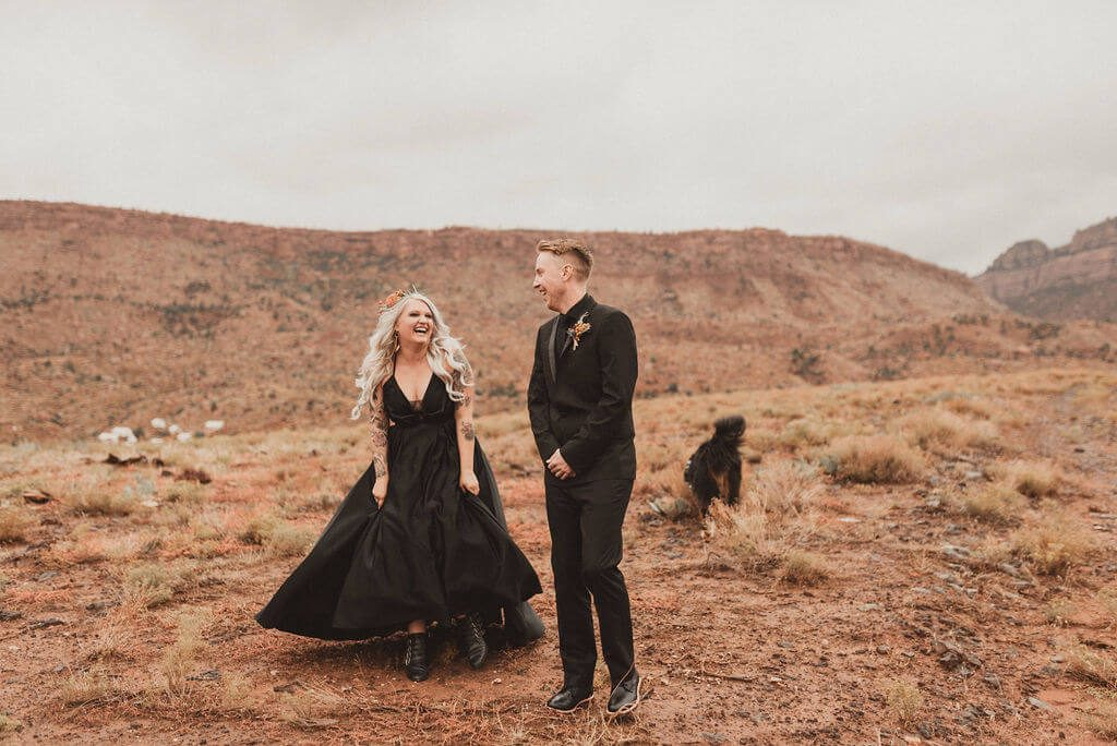 Tattooed Bride and groom in all black in desert at Zion Under Canvas. First look with the desert behind them before their epic glamping wedding,