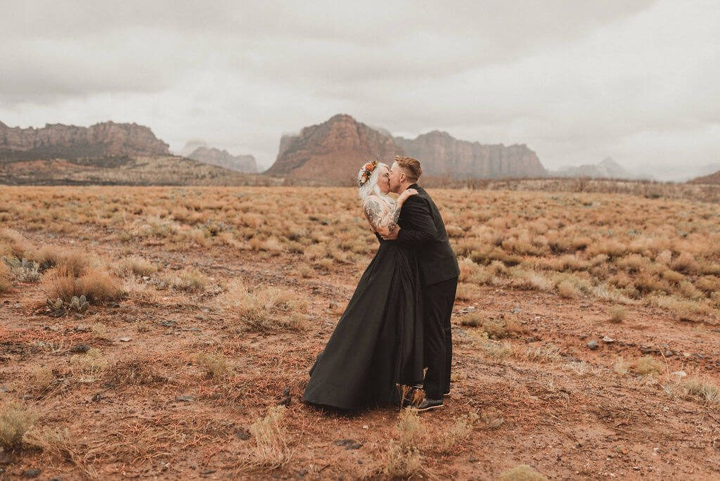 Bride and groom in all black kiss near Zion National Park before their epid 3 day glamping wedding