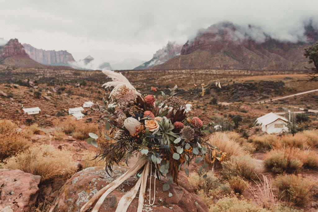 Moody fall bouquet with pampass grass, airplans and king protea at glamping wedding. Zion Under Canvas fall wedding