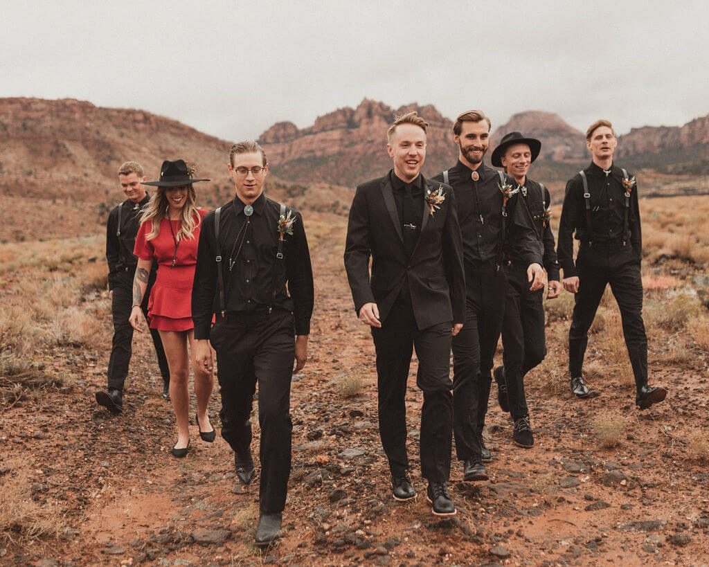 Groom in all black with groomsmen in all black and groomswoman in red. Zion Under Canvas desert wedding.