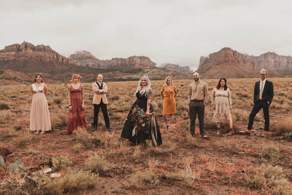 Bride in black wedding dress and her tribe out in the desert. Zion Under Canvas Wedding.