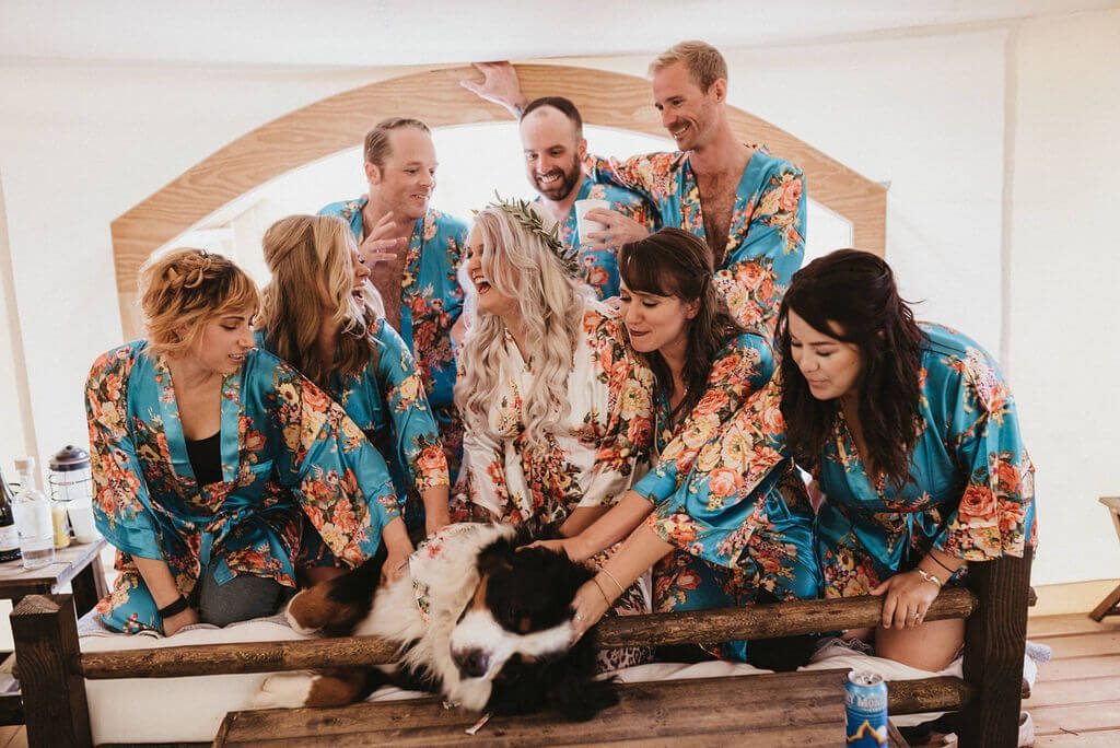 Bride and her bridesmaids and bridesman getting ready in a glamping tent with their dog Boom. Bridal party is wearing floral blue robes.