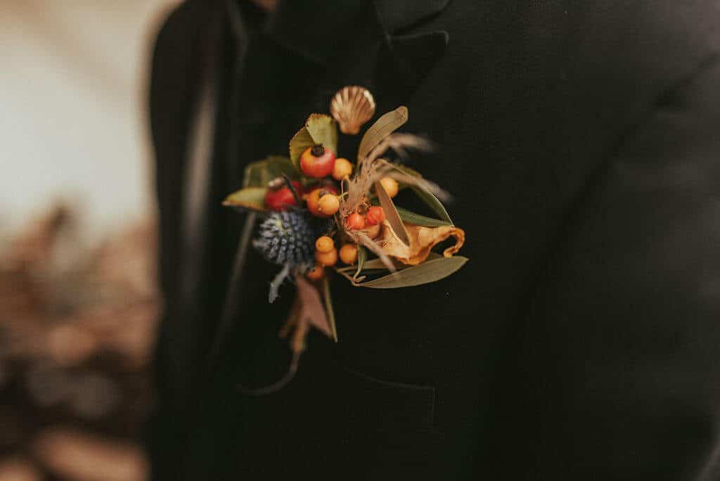 Groom's boutonniere with deep red berries, yellow and pops of blue