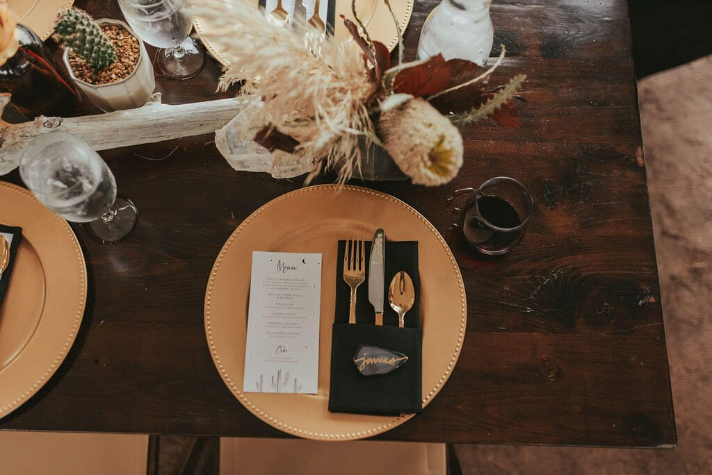 Wedding reception table with gold charger, black napkin, amber bud vases and dark flowers. Driftwood pieces on long wooden tables, pampass grass, king protea and cacti.