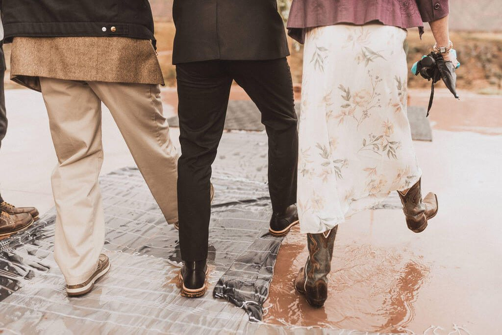 Groom walking through puddles on rugs as he walks down the aisle