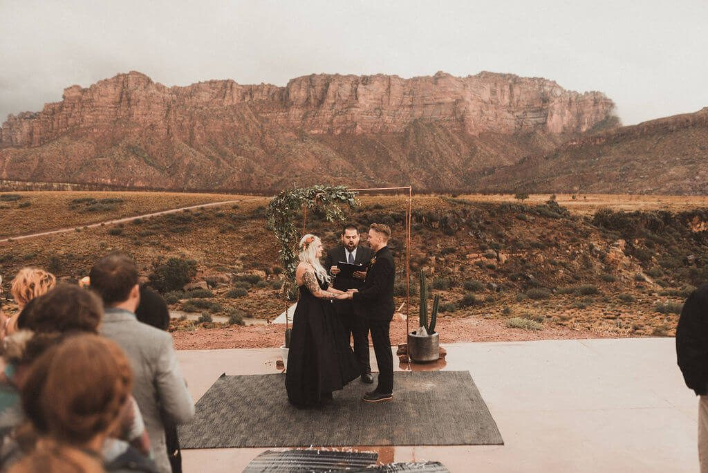 Bride and groom in all black in front of copper ceremony arch with greenery. Ceremony and reception at Zion Under Canvas for a glamping wedding