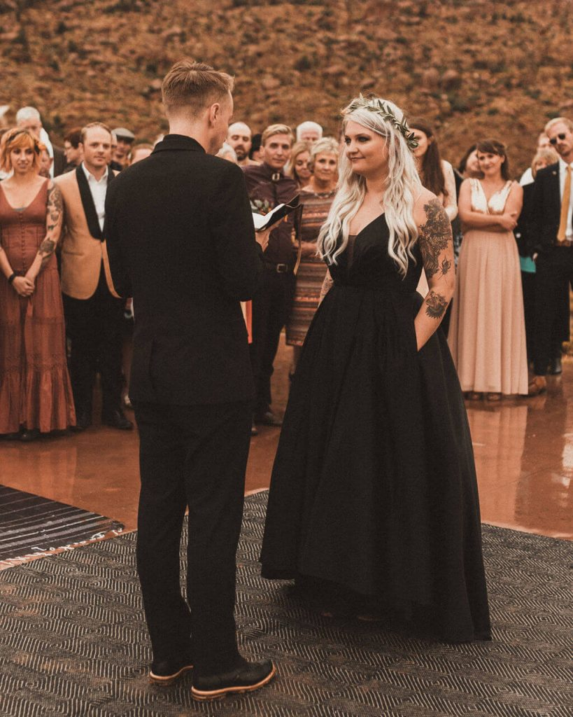 Bride tattooed in black dress with pockets during ceremony at Under Canvas Zion.