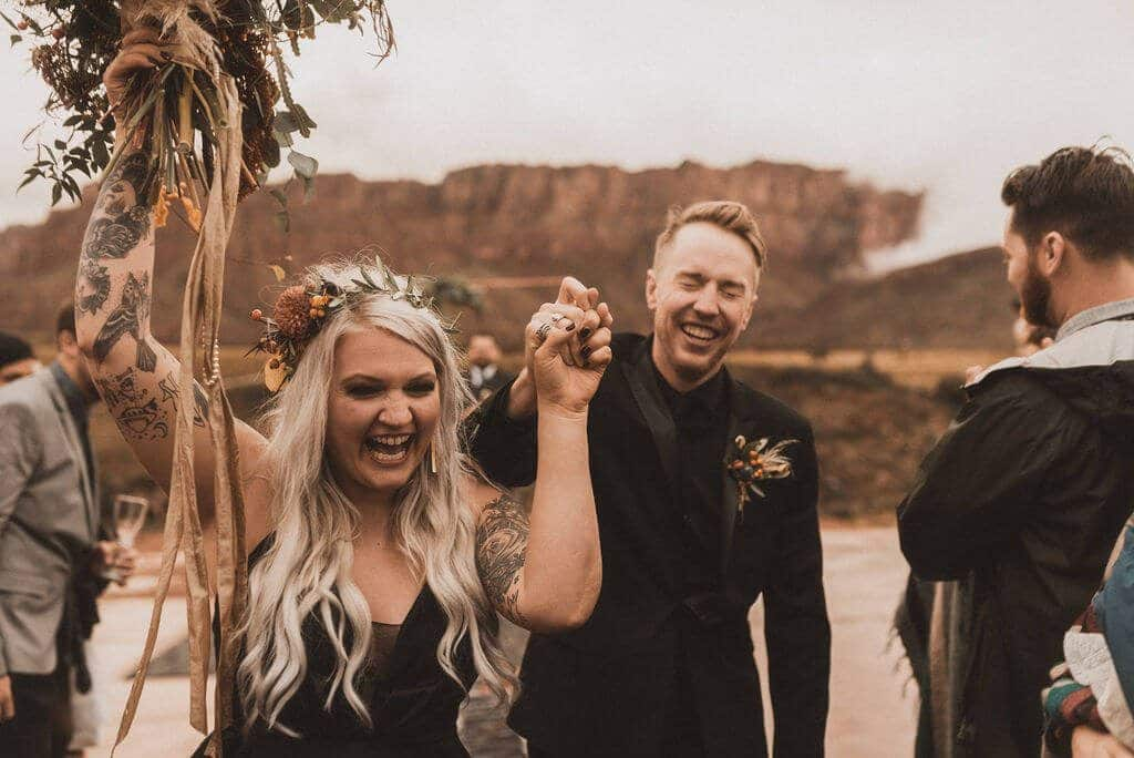 Bride and groom in all black laughing after ceremony