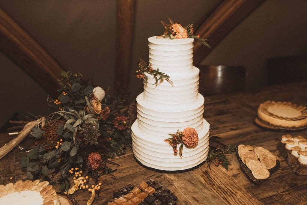 4 tiered simple white wedding cake with orange flowers and greenery