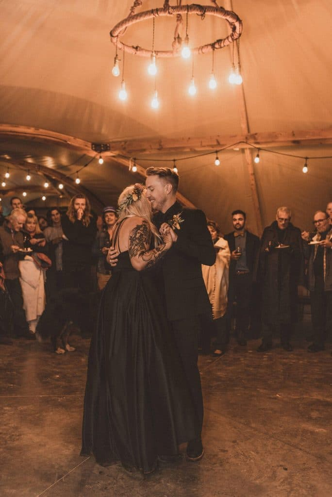 Tattooed bride and groom in all black doing their first dance in a teepee at Under Canvas Zion