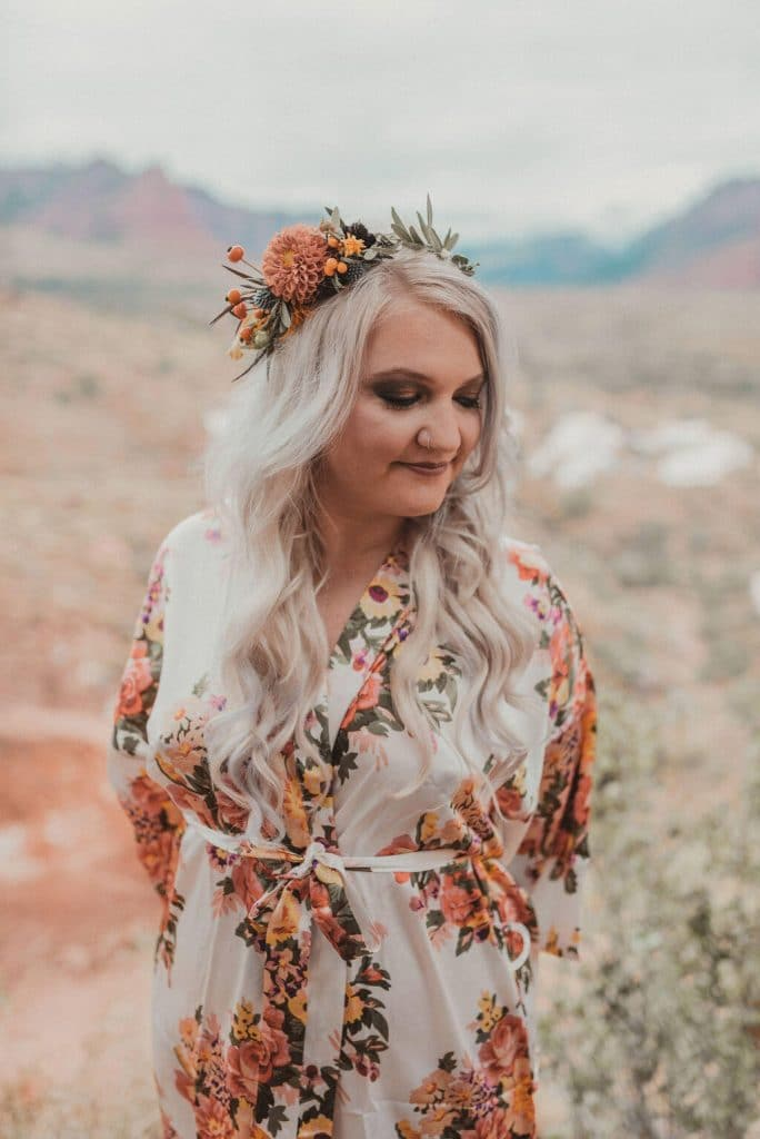 Blonde bride with flower crown and white floral robe at glamping wedding in Zion