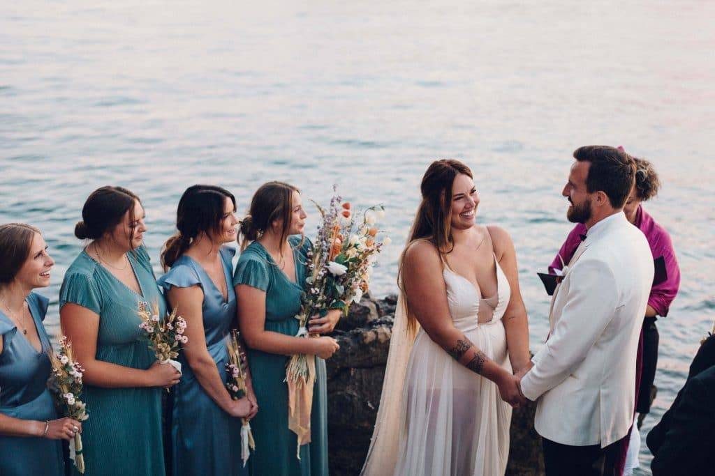 Intimate ceremony on the cliffside in Croatia at private AirBnB. Dusty blue bridesmaids dresses and deep v-neck bridal gown. Groom in white tux.