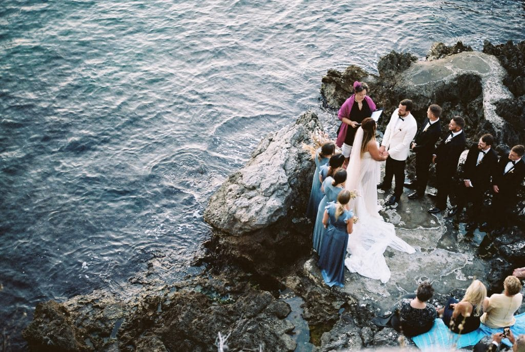 Intimate wedding in Croatia on the rocky cliffside. Bridesmaids in dusty blue dresses. Bride with dried bouquet and the adriatic sea behind them