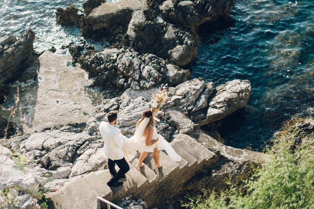 Groom helping bride down the rocky cliffs of Croatia after intimate wedding ceremony with 15 guests.