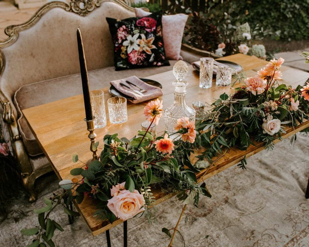 Sweetheart table with moody florals and black candlesticks. Green garland with peach flowers for wedding in Los Olivos.