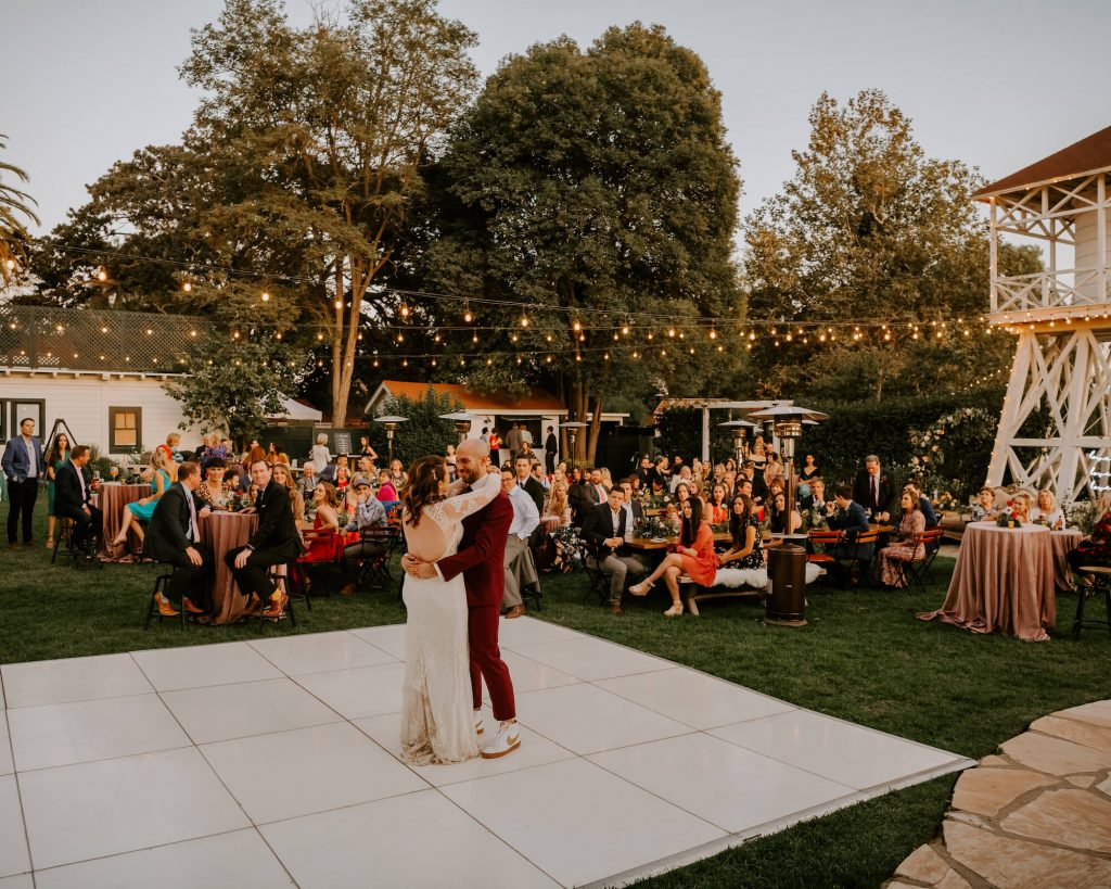 Bride and groom dance on white dance floor with string lights and moody florals with black candlesticks. Wedding by Cause We Can Events in Los Olivos