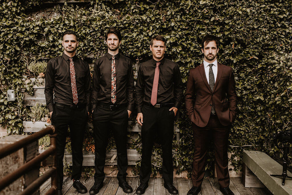 Groomsmen in black shirts and groom in dark red brown suit posing in front of plant wall at Smoky Hollow Studios