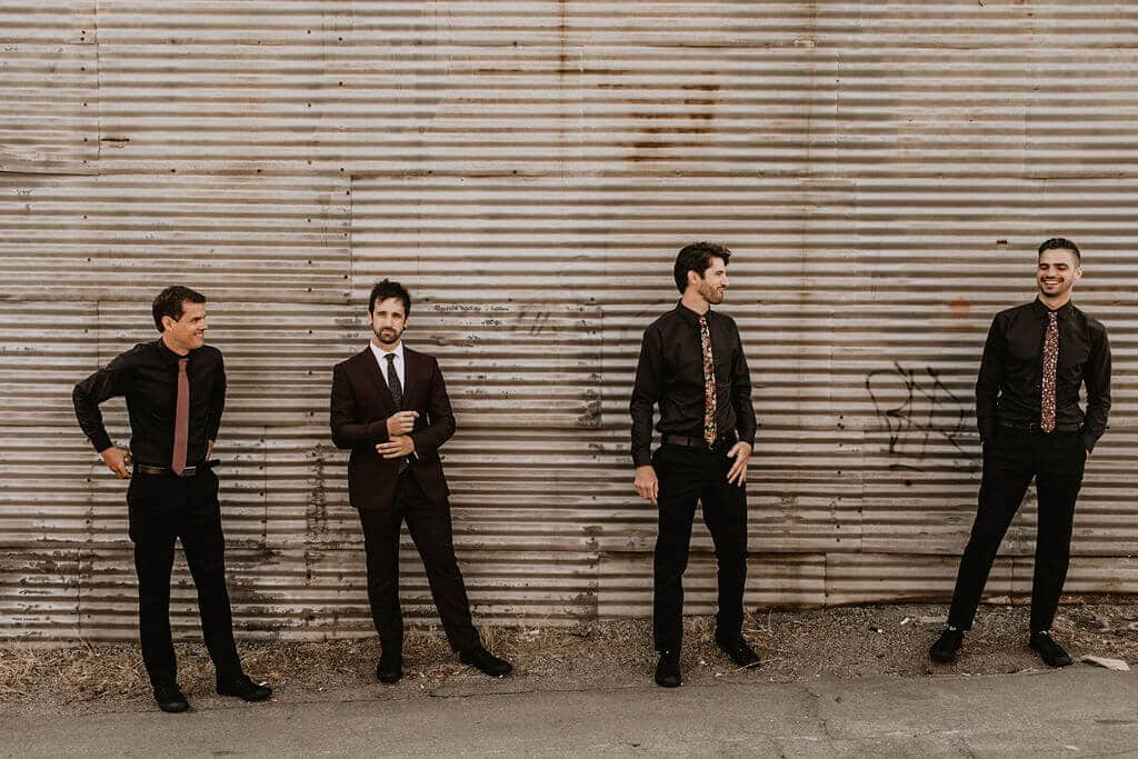 Groom and groomsmen in dark suits at Smoky Hollow Studio. Industrial warehouse wedding venue in Los Angeles