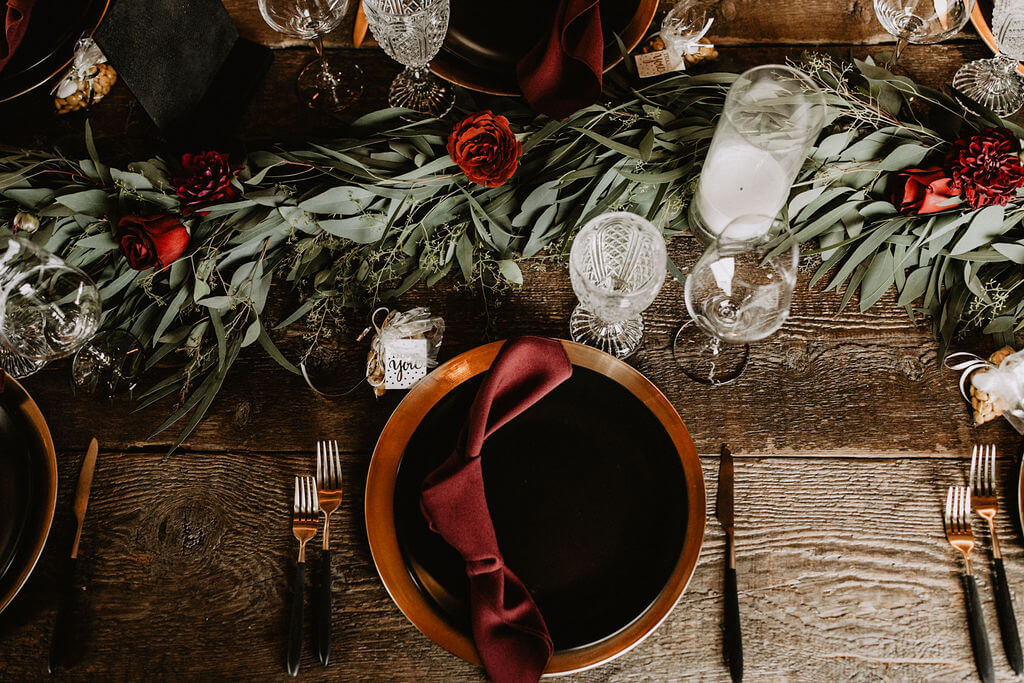 Black plate and gold charger with dark red knotted napkin. Green garland with dark red flowers is perfect for an industrial wedding at Smoky Hollow Studios