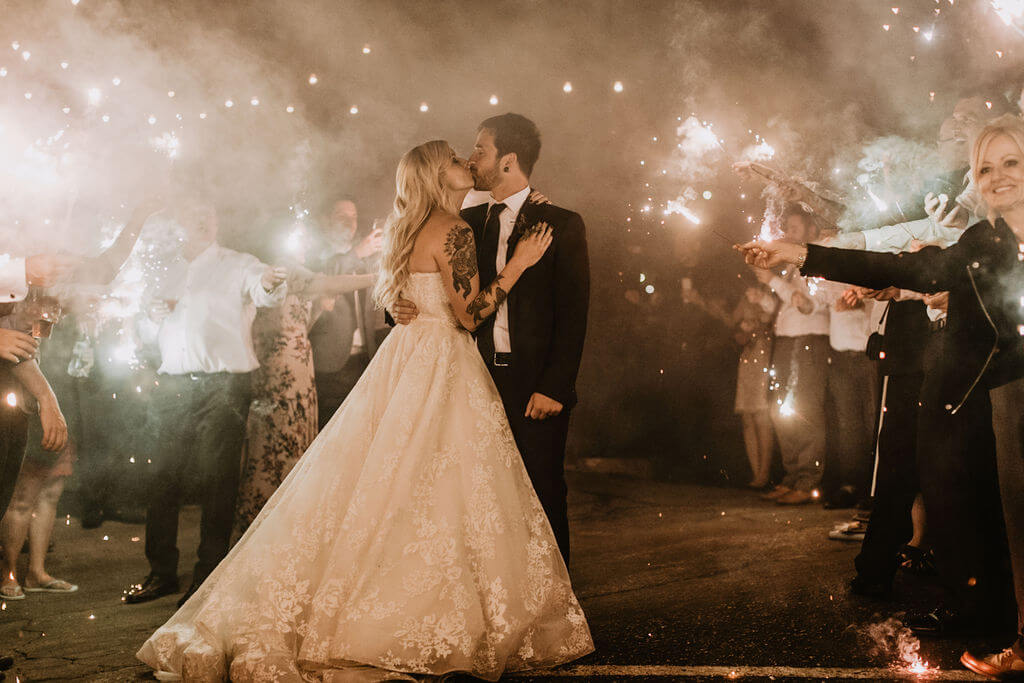 Bride and groom kiss at Sparkler grand exit at Smoky Hollow Studios