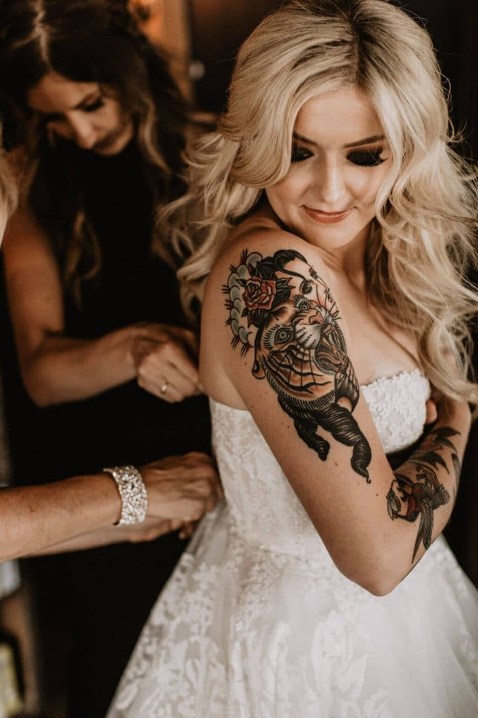 Tattooed bride getting into wedding dress at Smoky Hollow Studios