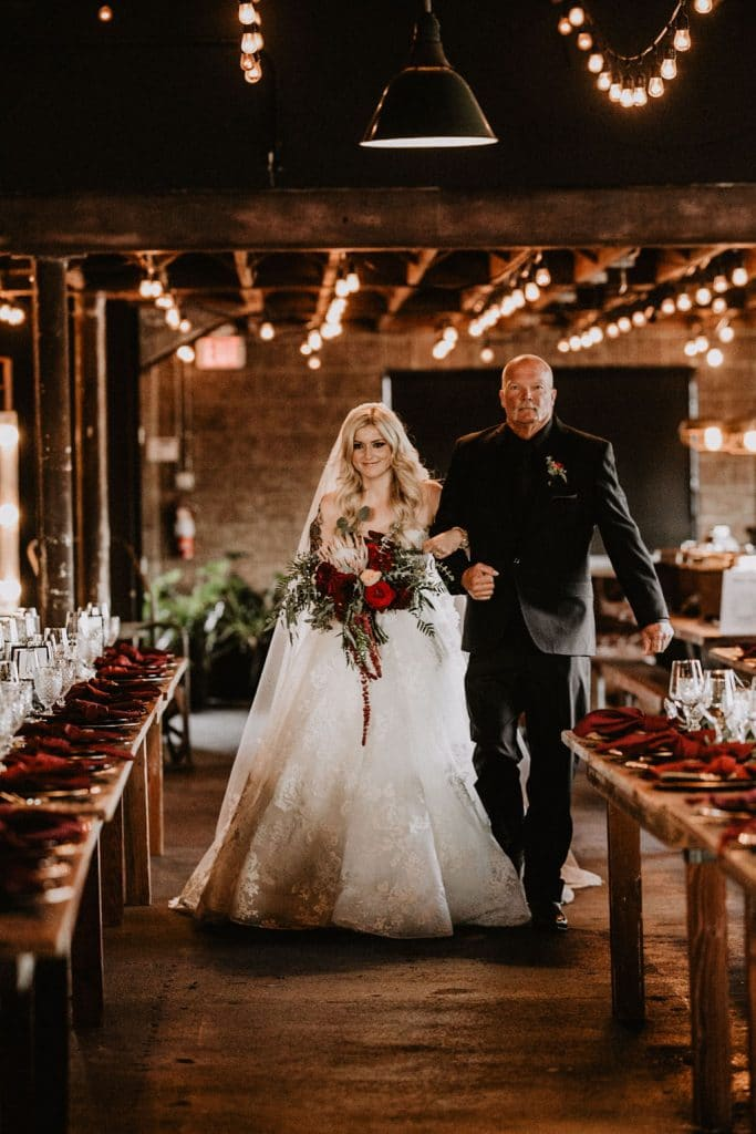 Bride with ballgown and tattoos walks down the aisle at industrial wedding venue Smoky Hollow Studios
