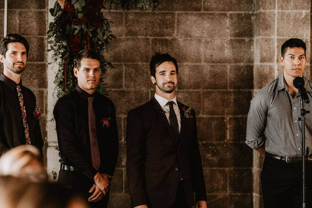 Groom in dark red brown suit waiting for his bride at the altar at Smoky Hollow Studios